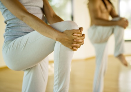 Yoga class standing holding knees
